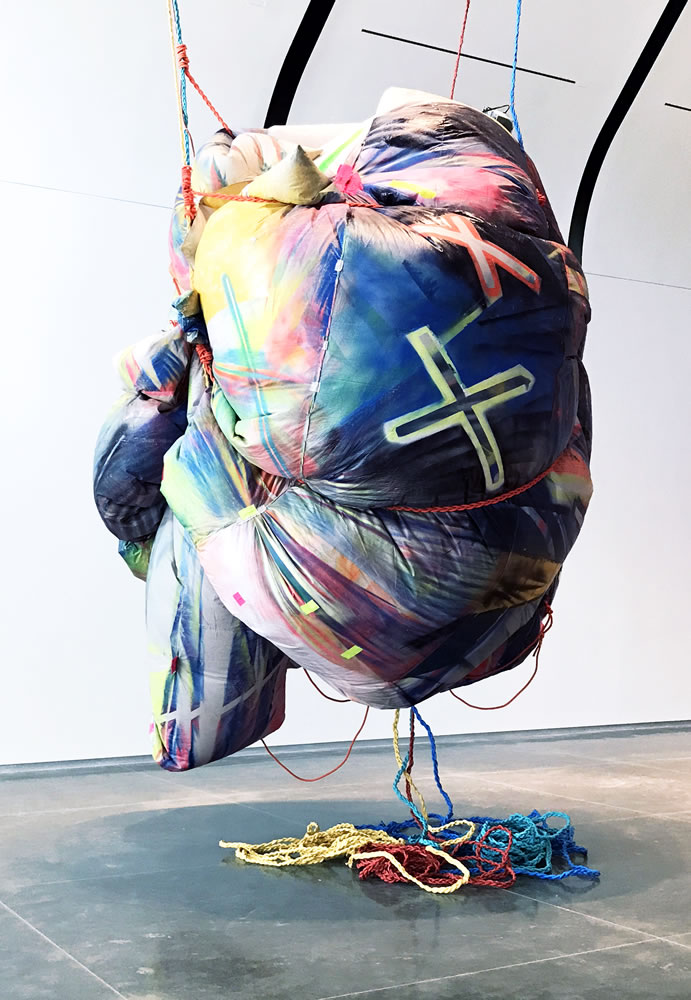 Claire Helen Ashley (born 1971). Hunnybunny (in a Pickle), 2016-2019. Approximately 216 x 144 x 144 inches. Installation view, How We See: Materiality and Color, Laumeier Sculpture Park, St. Louis, MO. Spray paint and duct tape on PVC coated canvas tarpaulin, ropes, and fan. Courtesy of the artist.