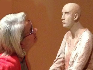 Image of patron examining a work of sculpture